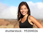 sporty outdoor mixed race woman smiling happy after workout running outside in mountain landscape. Portrait of fresh healthy multiracial Asian / Caucasian fitness model. - stock photo