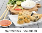 Oriental Snacks - Asian appetisers: wontons and spring rolls served with sweet chilli sauce. Cooking ingredients and rice on the background. - stock photo