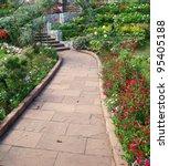 Stock photo stone walkway in flower garden 95405188