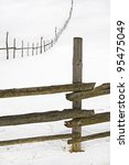 wooden fence for animals on a hill in winter - stock photo
