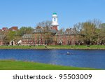 Harvard University in early spring. Green dome of Eliot House against clear blue sky, a rowboat in Charles River, people walking in the background. Beautiful college campus scenic.
