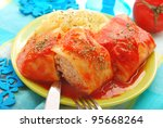 stuffed cabbage leaves rolled with minced meat and rice in tomato sauce as traditional polish dinner - stock photo