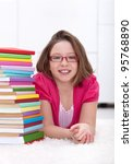 Young girl wearing glasses laying on the floor with lots of colorful books - stock photo
