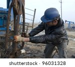 BAKU - AZERBAIJAN - JAN. 31: A roughneck grapples with a drilling rig in an oil production field near Baku, Azerbaijan, on Saturday, January 31, 2009. - stock photo