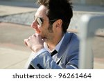 Smiling man dressed in suit sitting on the floor in the street - stock photo