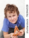 Boy with a slice of pizza sitting on the floor - stock photo