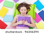 Young girl reading on the floor surrounded by colorful books - stock photo