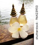 Spa Concept: bottles of essential oil & frangipani flowers - stock photo