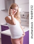 Young pregnant blonde woman talking via phone in kitchen - stock photo