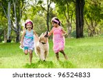 Stock photo two young girls running with golden retriever in park 96524833