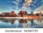 Teutonic castle in Malbork with reflection in frozen Nogat river, Poland - stock photo