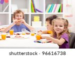 Kids around the table eating - stock photo