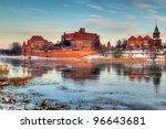 Teutonic castle in Malbork with frozen Nogat river, Poland - stock photo