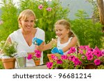 Gardening, planting concept - mother with daughter planting flowers into the flowerpot - stock photo