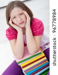 Young girl with headache sitting with lots of books - stock photo