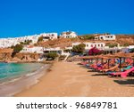sandy beach with colored sunbeds and thatched umbrellas in the Bay of Greek island. - stock photo