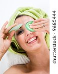Woman with Towel around head lifting on of the Eye-Pads and smiling nice to you. - stock photo