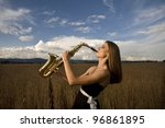 Young musician plays on saxophone in wheat field - stock photo