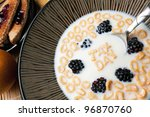 Bowl of cereal with blackberries and letter shaped pieces spelling the words TAX DAY floating in a milk. - stock photo