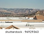 Roof tops of several commercial buildings a suburban background. - stock photo