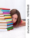 Young girl hiding behind stack of books - stock photo