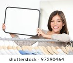 Shop sign woman. Small retail business owner showing blank sign in clothing store. For shopping or sale. Beautiful mixed race Caucasian / Chinese Asian woman in her twenties standing by clothes rack. - stock photo