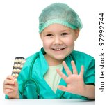 Cute little girl is playing doctor showing pills, isolated over white - stock photo