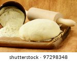 fresh dough with flour on wooden board - stock photo