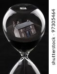 hourglass with house sinking into sand concept for housing market recession or housing difficulties - stock photo