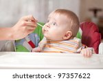 mother feeding baby food to baby | Shutterstock . vector #97357622