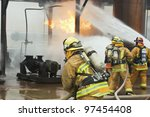 Selective focus is on the firefighter in the foreground. - stock photo