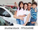Family holding keys to their new car at the dealer - stock photo