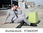 Man dressed in suit and suitcase sitting on the floor in the street - stock photo