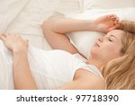 Young pregnant blonde woman sleeping in bed - stock photo