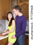 Happy young couple cooking at home kitchen together - stock photo