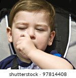 A baby in a stroller sucking his thumb ready for a nap. - stock photo