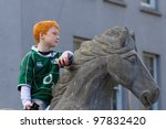 LIMERICK, IRELAND - MARCH 17: Unidentified boy on stone horse participates in a parade for St. Patrick's Day. It's a traditional Irish holiday celebration. March 17, 2012 in Limerick, Ireland. - stock photo