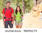 Hiking. Hiker couple portrait. Hikers walking in forest during camping travel hike. Healthy lifestyle photo of Asian woman and Caucasian man holding hands. - stock photo
