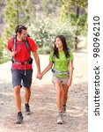 Couple hiking. Young hikers smiling happy holding hands walking in forest during camping travel. Asian woman, Caucasian man. - stock photo