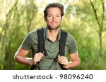 Young man hiking smiling happy portrait. Male hiker walking in forest. - stock photo