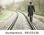 A Man Walking On The Tracks