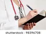 Doctor writes in working notebook - stock photo