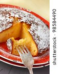 Delicious orange cake with sugar powder on a red rustic plate. - stock photo