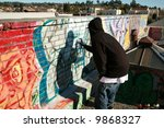 """an unidentifiable person spray paints graffiti on """"his own roof"""" so to avoid police problems for destroying property - stock photo"""