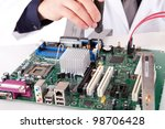 Computer engineer working on an old motherboard - selective focus - stock photo