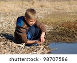 Young boy playing and getting muddy in a wetland pond - learning about nature by catching tadpoles, fish, shrimp and aquatic insects