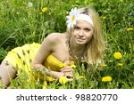 Beautiful young girl lying in field with camomiles. - stock photo