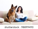 Stock photo portrait of beautiful young woman sitting on sofa with her german shepherd dog and netbook 98899493