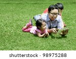 Happy Family: Father playing with a digital tablet. Shot outdoor on a sunny summer day - stock photo