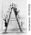 Group of women on tall ladder - stock photo